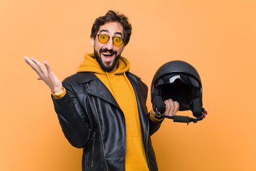 young crazy cool man rider, holding a motorbike helmet. Wall mural