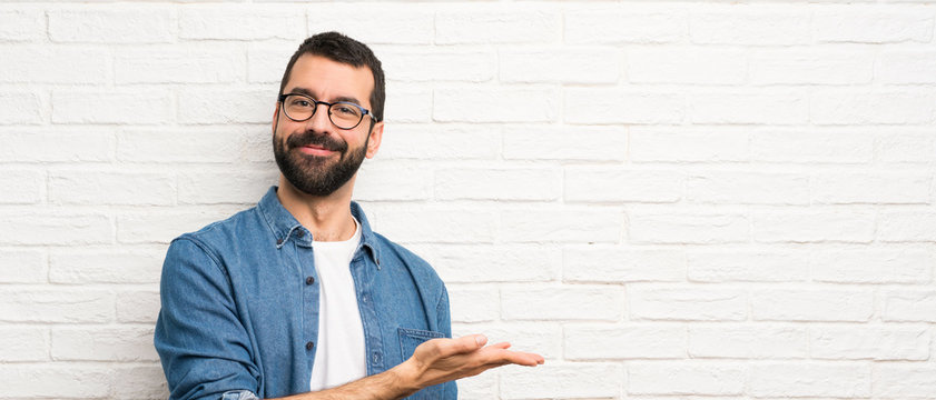 Handsome man with beard over white brick wall presenting an idea while looking smiling towards