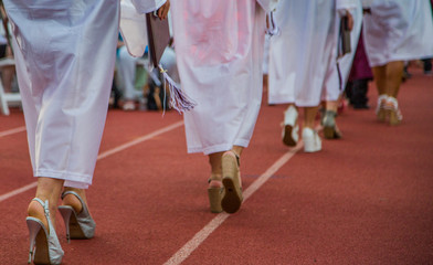 LOW SECTION OF women in graduation gowns