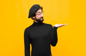 young french artist man feeling happy and smiling casually, looking to an object or concept held on the hand on the side against orange wall