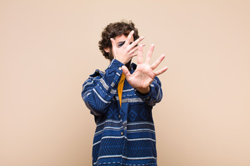 young crazy cool man covering face with hand and putting other hand up front to stop camera, refusing photos or pictures against flat wall