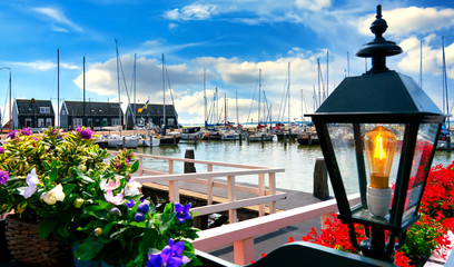 The harbor of Marken with flowers and lamp in foreground. Marken is a small historical dutch village in Netherlands