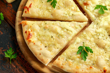Garlic cheese pizza on wooden board with herbs.