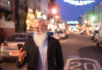 View of a attractive business man using smartphone. Cheerful smiling pensioner using smartphone having video call walking in street of modern city. Tech and joyful elderly lifestyle  - Image