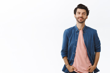 Cheerful, bearded handsome young man with messy hairstyle, standing relaxed in casual pose with hands in pockets, smiling, ordinary guy shopping in mall, buy gifts. Male look camera enthusiastic