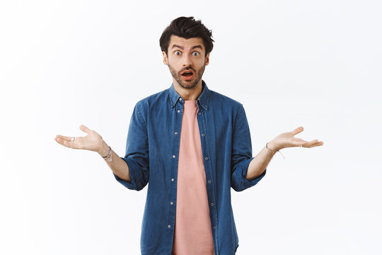 Surprised and confused young man cant understand what happened, shrugging and spread hands sideways indecisive, stare distressed and upset, open mouth popping eyes camera shocked
