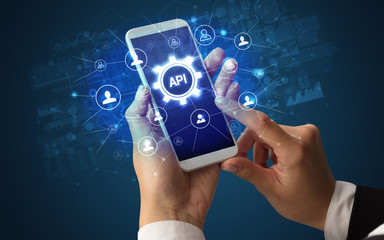 Female hand holding smartphone with API abbreviation, modern technology concept