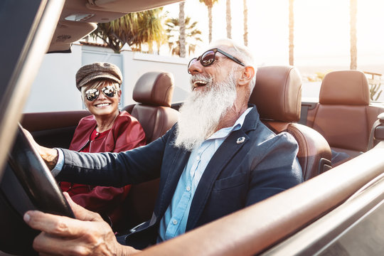 Happy senior couple having fun on new convertible car - Mature people enjoying time together during road trip vacation - Elderly lifestyle and travel transportation concept