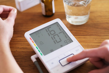 Young woman with hypertension is controlling her blood pressure.