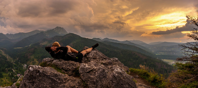 Man Relaxing On Mountain Against Cloudy Sky During Sunset