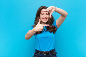 young pretty woman feeling happy, friendly and positive, smiling and making a portrait or photo frame with hands against blue wall