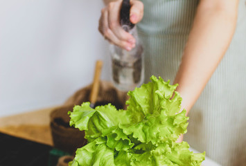woman watering a green salad