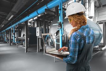 Engineer woman with laptop inspect modern industrial gas boiler room. Heating gas boilers,...