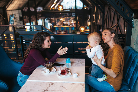 Two friends enjoying in cafe bar with cute little baby boy.