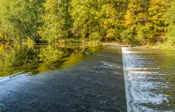 weir on a river surrounded with trees