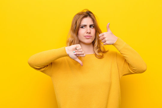 young pretty blonde woman feeling confused, clueless and unsure, weighting the good and bad in different options or choices against yellow wall