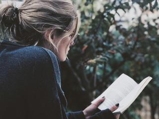 Close-Up Of Woman Reading Novel