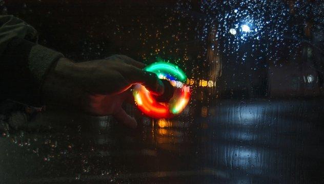 Cropped Image Of Hand Holding Illuminated Spinner
