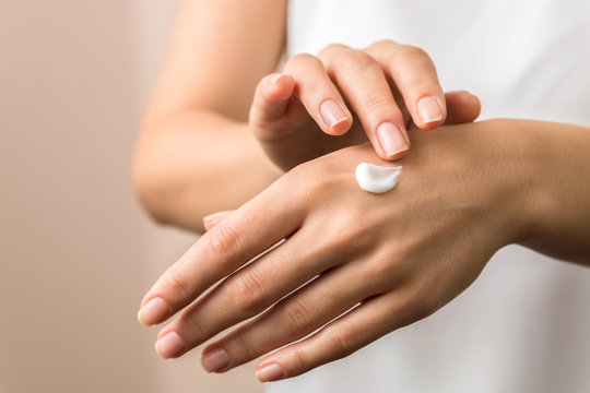 closeup view of woman hands applying hand cream. beauty shot