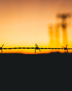Close-Up Of Silhouette Barbed Wire Against Sky At Sunset
