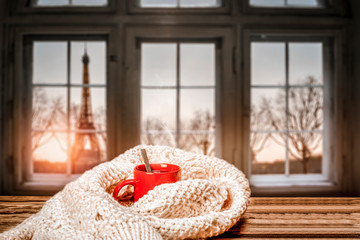Wall Mural - Romantic photo of Valentine's Day red mug on wooden table.Free space for your decoration.Blurred retro old window sill with landscape of Paris city at February.Sun light of orange color and copy space
