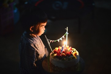Boy With Birthday Cake On Table In Darkroom
