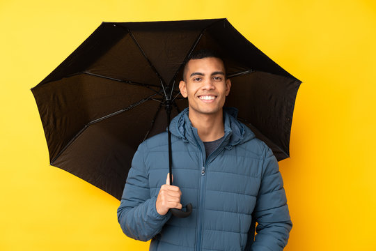 Young handsome man holding an umbrella over isolated yellow background smiling a lot