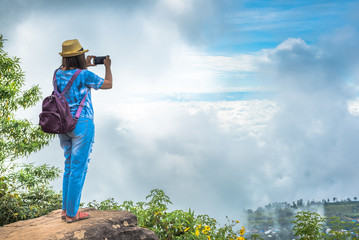 Traveller woman take photo with smartphone on the top of mountain.