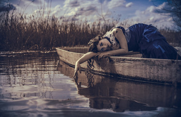 Portrait Of Woman In Boat On Lake Against Plants