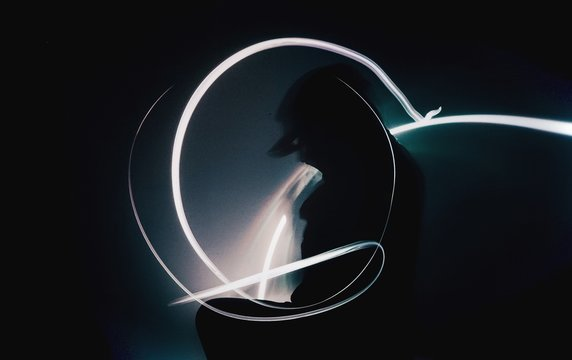 Silhouette Woman Standing Amidst Light Trails At Night