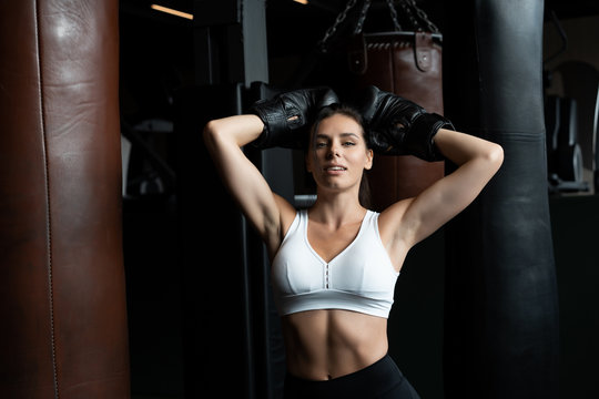 Boxing woman posing with punching bag, on dark background. Strong and independent woman concept