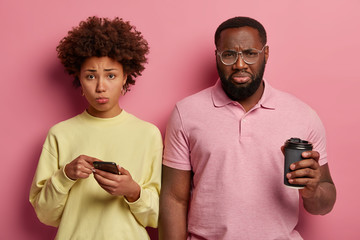 Photo of desperate sullen Afro American couple read bad news in social networks, drink takeaway coffee, sad woman points at display of smartphone, has some problems, isolated over pastel pink wall