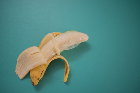 Directly Above Shot Of Banana Wearing Condom Over Blue Background