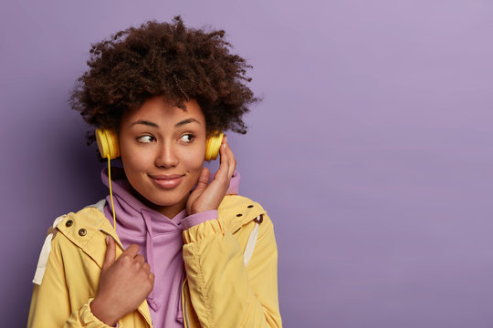 Pretty dark skinned hipster girl listens audio book in headphones, focused aside with dreamy expression, wears casual clothing, isolated on purple wall with blank space. People, leisure time