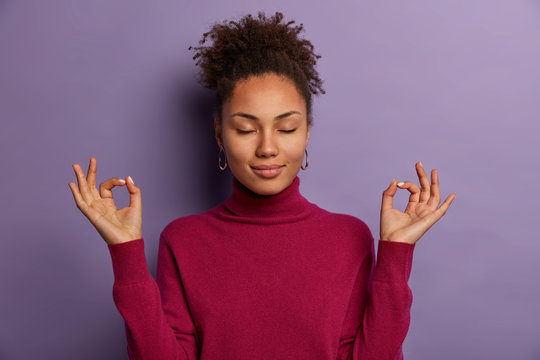 Portrait of good looking woman meditates, keeps both hands in okay gesture, keeps eyes closed, practices yoga to relax after work, wears burgundy jumper, isolated on purple wall. Zen posture