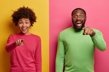 You are what we need. Positive surprised Afro American woman and man smile broadly and indicate directly at camera, make choice, choose you with happy faces, wear bright clothing. Colorful image