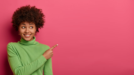 Go right there. Joyful friendly woman shows direction to shop, explains way, points fore finger on empty space, wears green jumper, poses against pink wall with copy place for advertising content Fotomurales