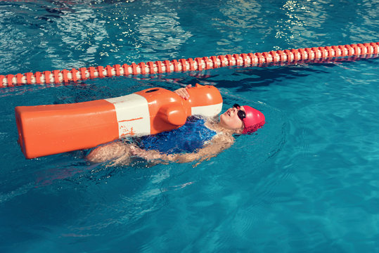 High Angle View Of Girl Swimming With Dummy In Pool