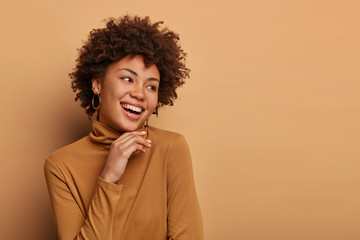 Curly haired woman looks joyfully aside, touches chin gently, has broad toothy smile, enjoys nice live dialogue with someone, wears casual clothing, stands enthusiastic against brown background