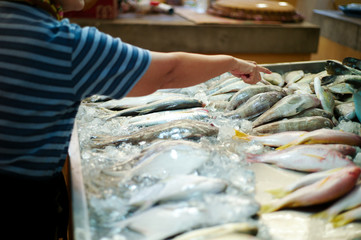 Closeup crowd of dead fish on the tray in the fresh market with blurred hand of female buyer selecting the fish