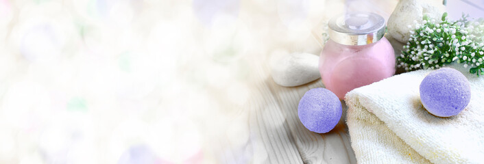 Mock up spa aromatherapy concept with lavender bath bombs, scrub, towel,  stones and flowers. Still life or body care cosmetics banner.