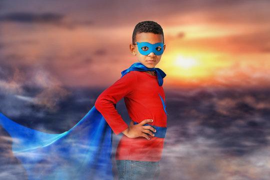 Cute African-American boy dressed as superhero against sky