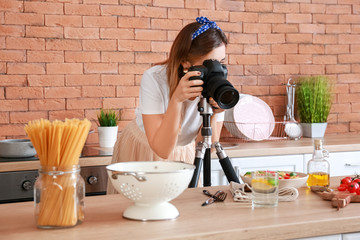 Young photographer taking picture of pasta in kitchen