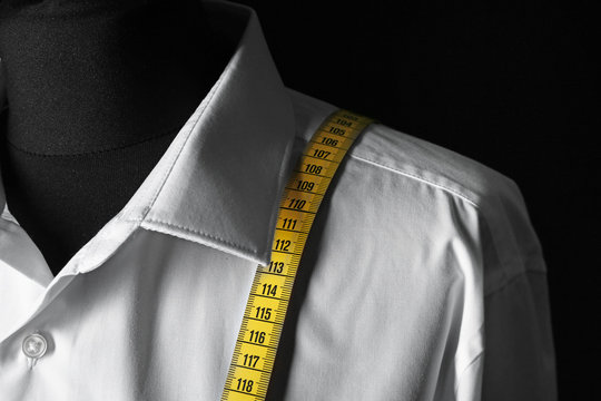 Mannequin with custom tailored shirt and measuring tape on dark background, closeup