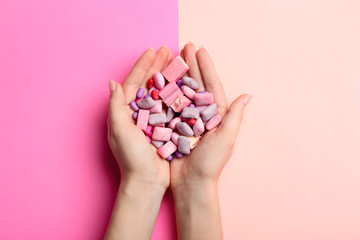 Female hands with chewing gums on color background