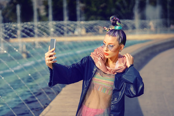 Cool funky hipster young fashion influencer girl with crazy hair and avant garde style taking selfie on street