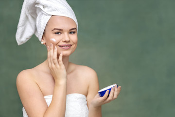 Smiling young woman applying moisturizer on face for healthy skin