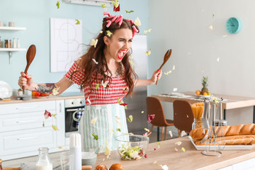 Funny angry housewife cooking in kitchen