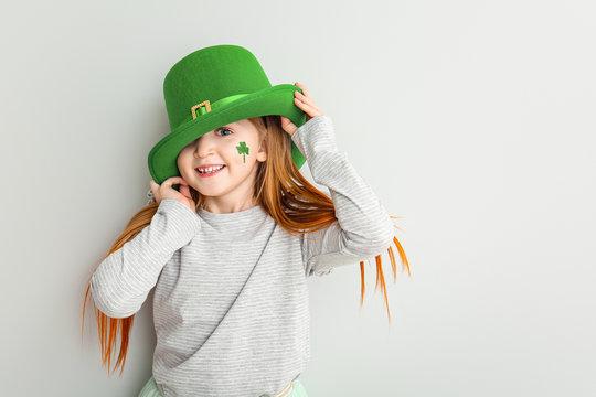 Funny little girl on white background. St. Patrick's Day celebration