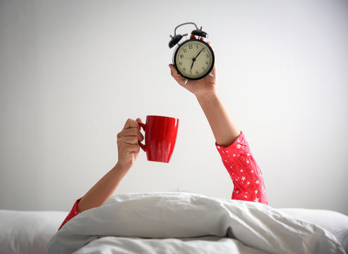 Woman with cup and alarm clock lying in bed, closeup. Morning time